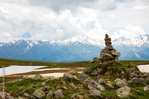 pyramid of stones on background of  mountain with snow - 221386452