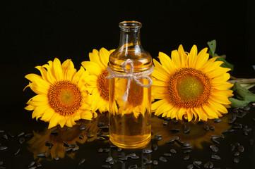 Sunflowers with oil on black background © alekseenko