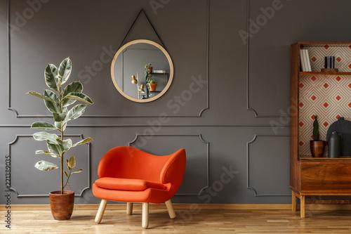 Jasny pomarańczowy fotel, retro drewniana szafka i lustro na szarej ścianie z formowaniem w stylowym wnętrzu salonu z miejscem na kopię do lampy. Prawdziwe zdjęcie.