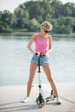 young blonde woman in pink top, shorts and sunglasses on blue kick scooter posing to camera