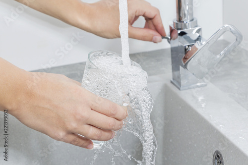 Hand holding a glass of water poured from the kitchen faucet. - 221393032