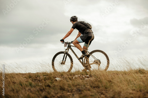 cyclist with backpack on mountainbike biking on field dry grass