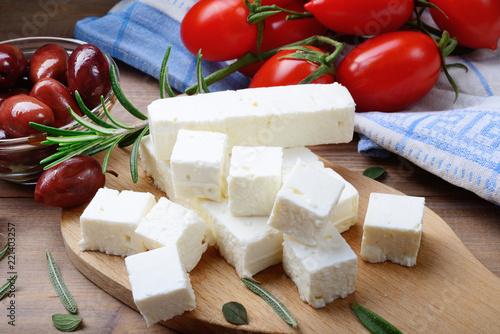 Fototapeta Feta cheese with kalamata olives, tomatoes and rosemary on wooden background