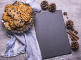 Delicious freshly baked Christmas cookies with black board for recipe on a gray wooden table. - 221405869