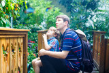 Father and preschool kid boy discovering flowers, plants and butterflies at botanic garden. Family, young man and son interested in biology. Active educational leisure with preschool kids in museum - 221409026