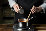 Cooking tomato sauce in metal saucepan by man cook hands, steps process on black background copy text recipe. - 221416899