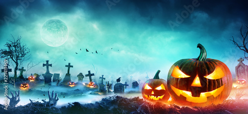 Leinwanddruck Bild Jack O Lanterns And Zombie Hands Rising Out Of A Graveyard In Misty Night