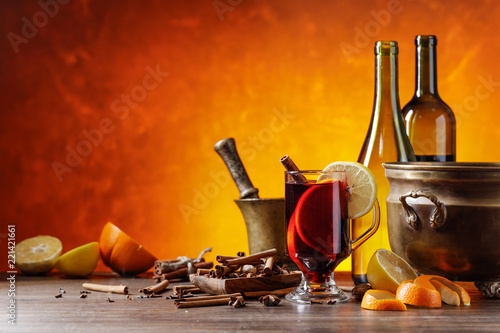 Mulled wine with spices and citrus fruits on a kitchen table with utensils. - 221421661