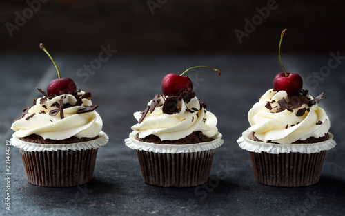 delicious sweet cupcakes decorated with cream, chocolate and fresh cherry. - 221424219