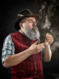 dramatic portrait of gray bearded senior man in hat smoking tobacco pipe. view of Austrian, Tyrolean, Bavarian old man in national traditional costume in retro style. - 221427823