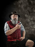 dramatic portrait of gray bearded senior man in hat smoking tobacco pipe. view of Austrian, Tyrolean, Bavarian old man in national traditional costume in retro style. - 221428008