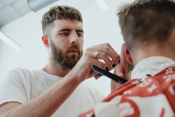 Handsome bearded man in barbershop. Barber cuts hair with  electric trimmer.