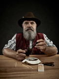 The senior bearded man sitting at table and clogging the tobacco in pipe. The male hands close up. Bavaria. a man dressed in traditional Bavarian or Austrian national traditional costume - 221429435