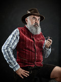 dramatic portrait of gray bearded senior man in hat smoking tobacco pipe. view of Austrian, Tyrolean, Bavarian old man in national traditional costume in retro style. - 221430893