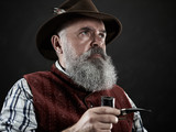 dramatic portrait of gray bearded senior man in hat smoking tobacco pipe. view of Austrian, Tyrolean, Bavarian old man in national traditional costume in retro style. - 221431883