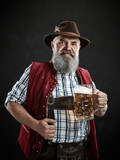 Germany, Bavaria, Upper Bavaria. The smiling man with beer dressed in in traditional Austrian or Bavarian costume in hat holding mug of beer at studio - 221432042
