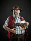 Germany, Bavaria, Upper Bavaria. The smiling man with beer dressed in in traditional Austrian or Bavarian costume in hat holding mug of beer at studio - 221432061