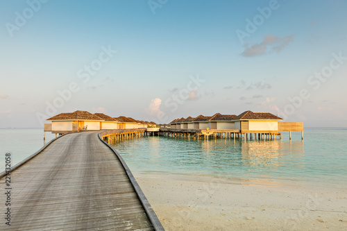 Wooden pier, jetty at tropical island resort in early morning, Maldives. Vacations And Tourism Concept