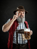 Germany, Bavaria, Upper Bavaria. The smiling man with beer dressed in in traditional Austrian or Bavarian costume in hat holding mug of beer at studio - 221432473