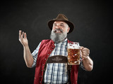 Germany, Bavaria, Upper Bavaria. The smiling man with beer dressed in in traditional Austrian or Bavarian costume in hat holding mug of beer at studio - 221432630