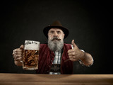 Germany, Bavaria, Upper Bavaria. The smiling man with beer dressed in in traditional Austrian or Bavarian costume in hat holding mug of beer at studio - 221432880