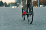 Closeup of casual man legs riding classic bike on city road - 221435632