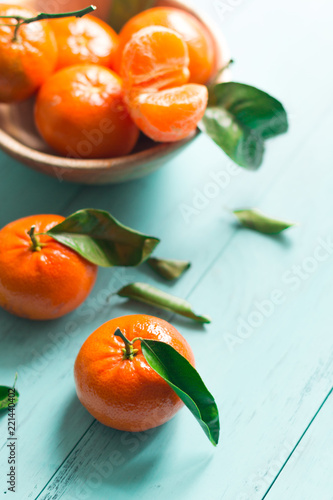 Tangerines with green leaves in a wooden bowl - 221440402