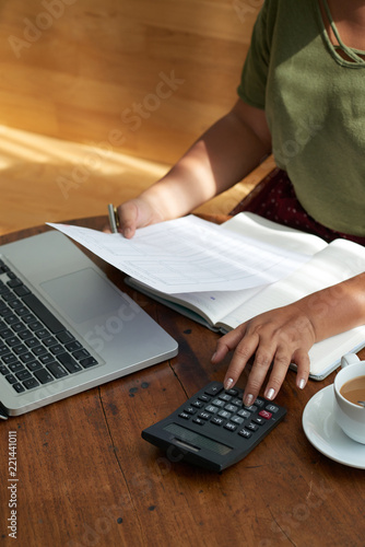 Unrecognizable female using calculator and reading papers while sitting at table in cozy cafe - 221441011