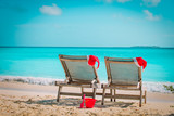 Christmas on beach -chair lounges with Santa hats at sea - 221442442