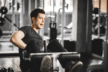 Fit handsome caucasian man sit up on machine in sportswear. Young man sit up exercise to strengthen their core abdominal muscles at fitness training in gym. Healthy, Sports, Lifestyle, Fitness concept © Phawat Topaisan