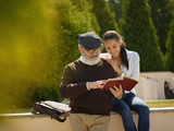 Help someone you love. Portrait of young smiling girl embracing grandfather with book against city park. community and family lifestyle concept - 221453499