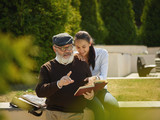 Help someone you love. Portrait of young smiling girl embracing grandfather with book against city park. community and family lifestyle concept - 221453651