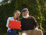 Help someone you love. Portrait of young smiling girl sitting with grandfather and laptop against city park. community and family lifestyle concept - 221453803