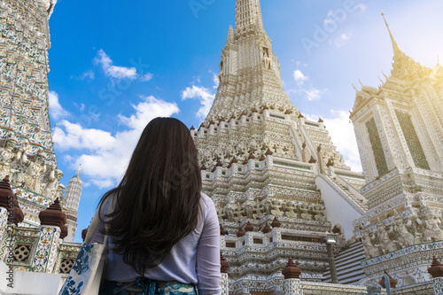 Foto Murales Woman tourist is looking at the Pagoda inside Wat Arun temple in Bangkok, Thailand during holiday vacation time.