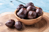 Whole inshell nutmeg nuts in a bowl on blue rustic wooden table. - 221466848
