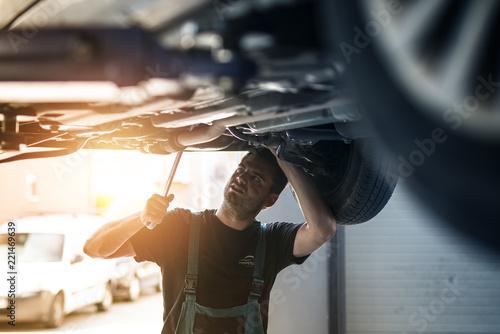 obraz lub plakat Car mechanic repairing vehicle using wrench tool in his workshop.