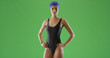 Young black female swimmer in one piece swimsuit and swim cap on green screen