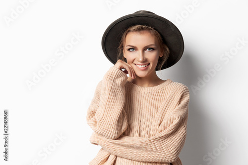 Leinwanddruck Bild Portrait of attractive young smiling woman feeling comfortable and cosy in nice light pullover. Casual autumn style concept. Isolated on white background