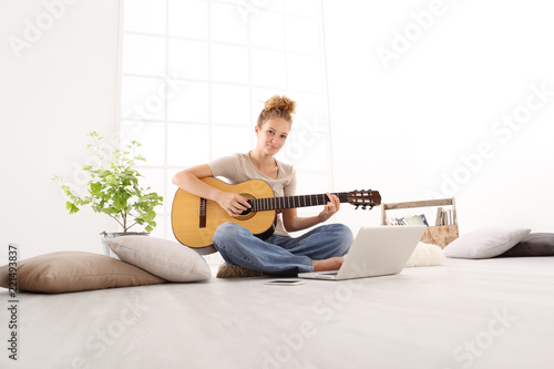 Beautiful smiling young woman playing guitar with computer, learn to play with an online course, sitting on the floor in casual clothes at home