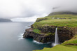 View of Mulafossur waterfall and Gasadalur village, Faroe Islands - 221498624