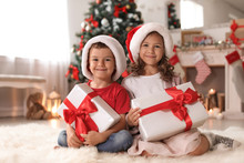 "Постер, картина, фотообои ""Cute little children in Santa hats with Christmas gift boxes at home"""