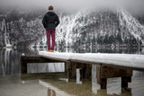 View from behind of a young man standing at the end of a snowy wooden pier - 221505628