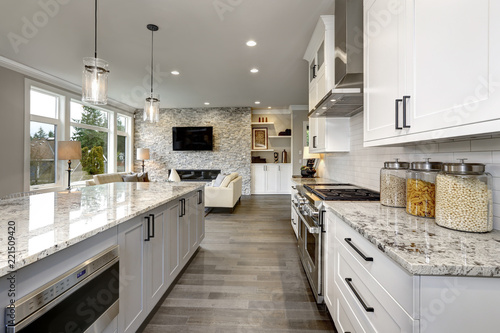 Beautiful kitchen in luxury home modern  interior with island and stainless steel chairs - 221509420