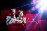 Romantic couple cuddling and watching the miraculous part of the film - 221514076