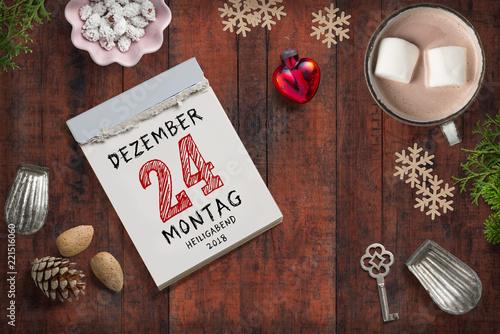 weihnachtliche Dekoration und Abreißkalender mit dem 24.12.2018 auf rustikalem Holzuntergrund - 221516060
