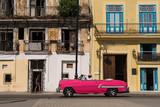 Un carro antiguo de color rosado circula por el casco histórico de la Habana.