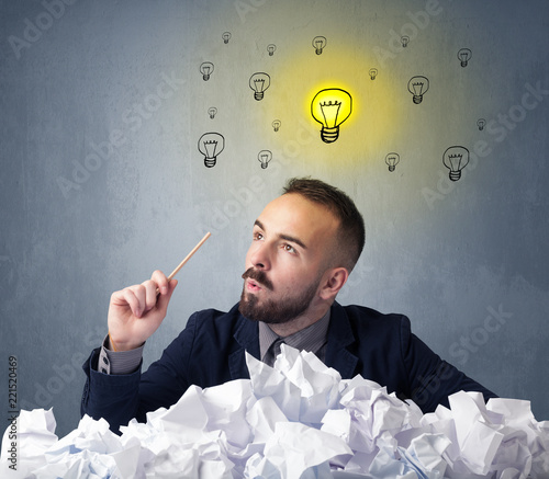 Young businessman sitting behind crumpled paper with lightbulbs above his head