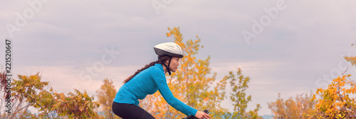 Biking in fall autumn nature Asian cyclist girl riding bicycle doing outdoor sport in cold weather. Panoramic banner.