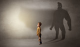 Cute kid in a room with plush on his hand and hero shadow on his background  - 221521480