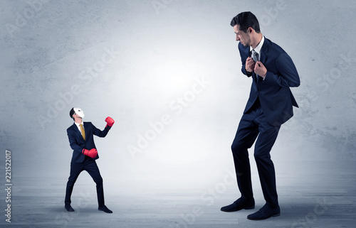 Leinwanddruck Bild Big businessman being afraid of small masked businessman with box gloves in an empty room concept